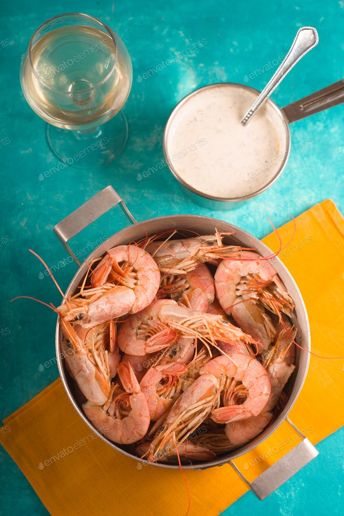 Shrimps on a yellow napkin, glass with white wine and sauce