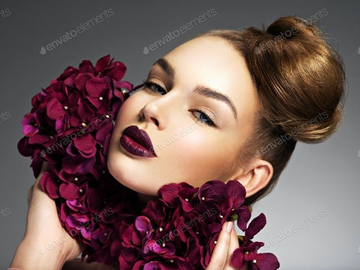 Beautiful young woman with a nice hairstyle and flowers.