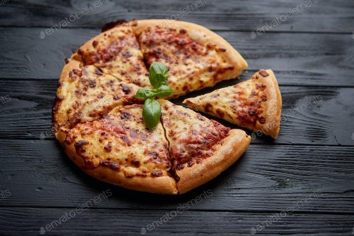 Geschnittene Pizza Margarita mit Basilikumblättern