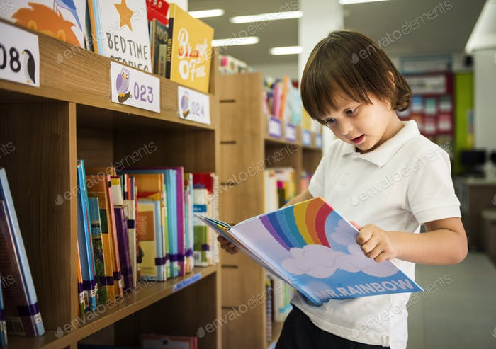 Young Boy Reading Kinder Story-Buch in Bibliothek