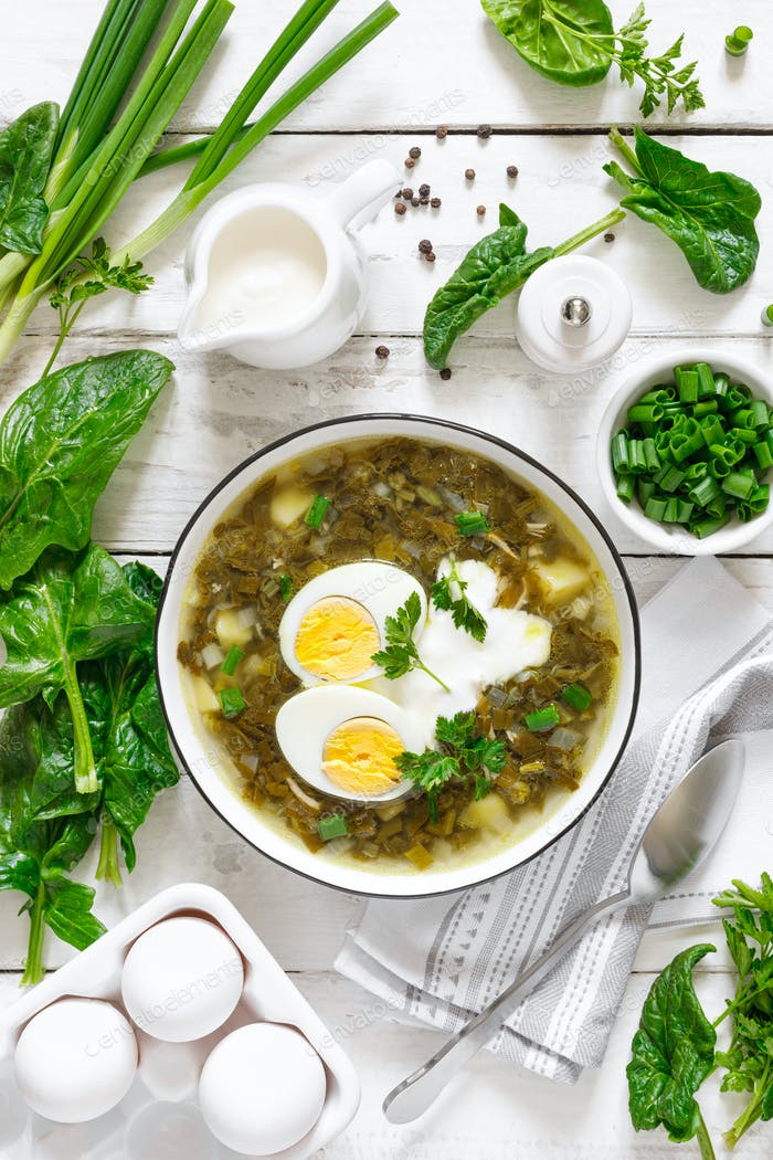 Green sorrel and spinach soup with boiled egg and sour cream on white wooden rustic table, top view