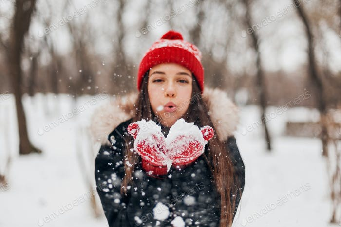 happy woman in red mittens and knitted hat wearing winter coat, walking in park, playing with snow