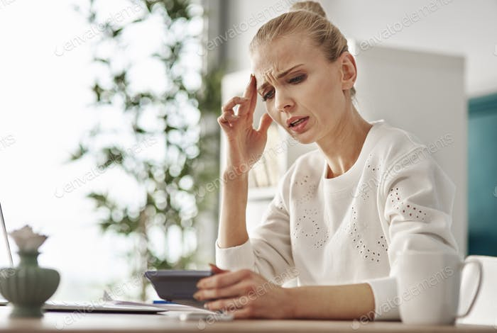 Worried woman with calculator at home office