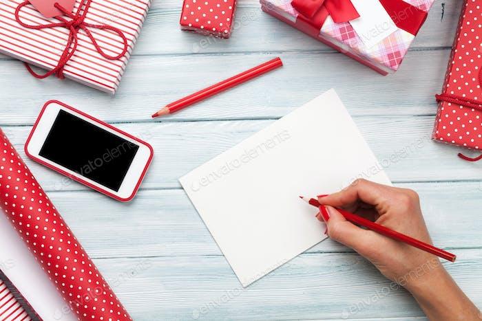 Tarjeta de felicitación de escritura Mujer y envolver regalos de Navidad