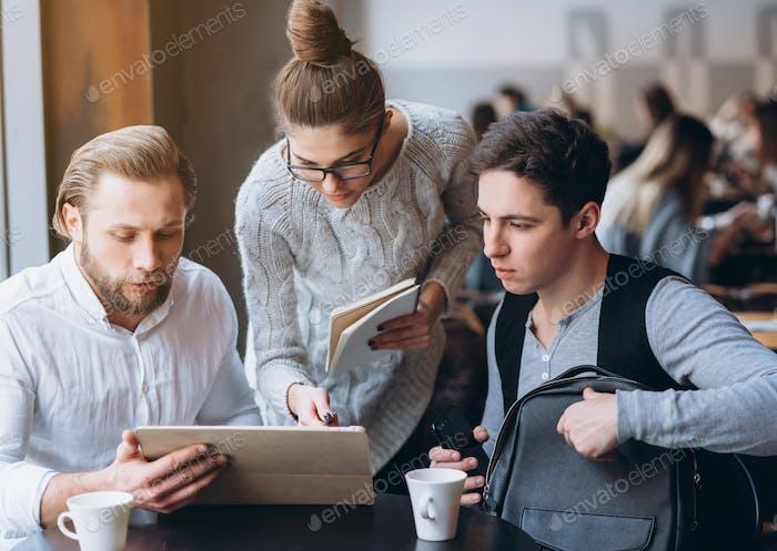 Drei Geschäftsleute arbeiten im Café