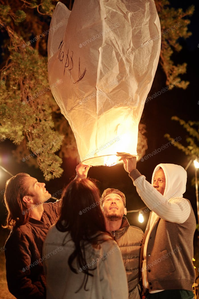 Intercultural young friends holding and looking into large illuminated balloon