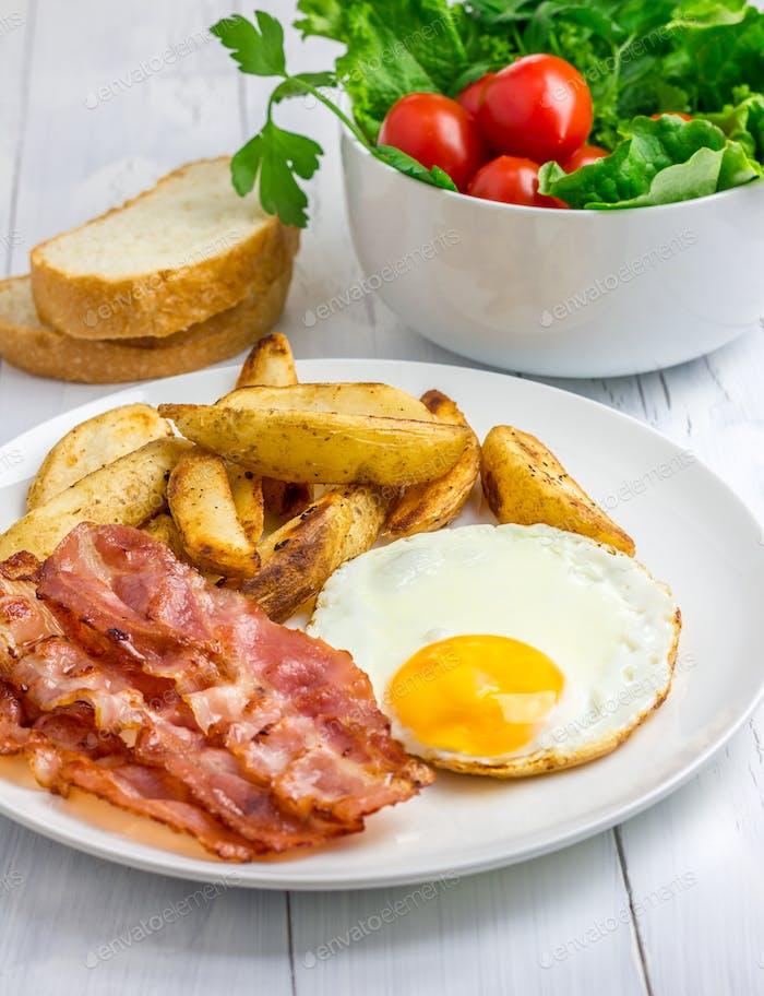 Herzhaftes Frühstück mit Speck, Spiegelei, Kartoffel und Gemüse
