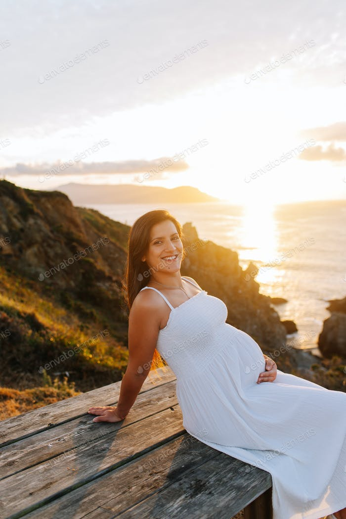 Portrait of a pregnant woman against an oceanic landscape