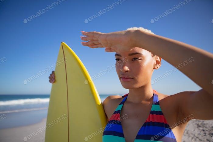 Schöne afrikanische Frau im Bikini mit Surfbrett Abschirmung Augen am Strand in der Sonne