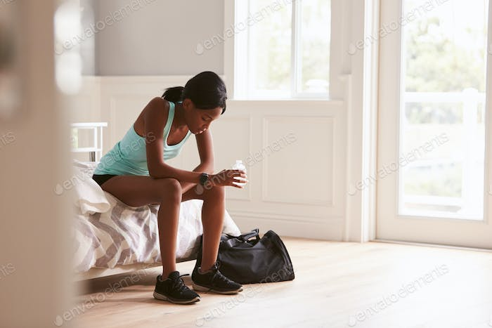 Young woman in sports clothes sitting at home drinking water
