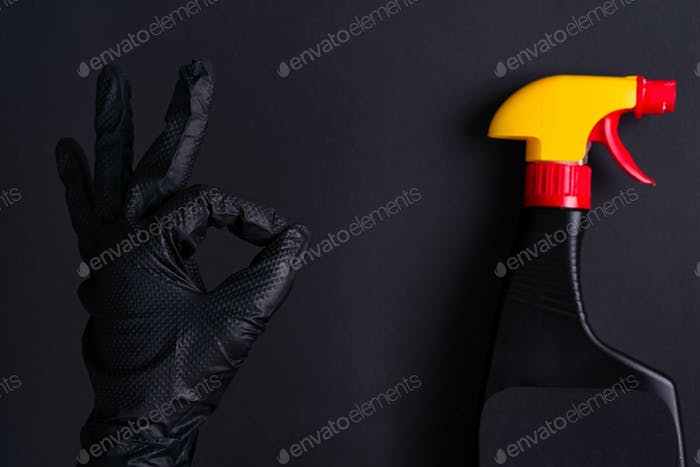 Woman's hand in a black latex glove for cleaning making an OK sign and plastic spray bottle on