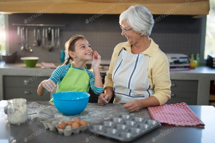 Granddaughter showing eggs to grandmother and smiling