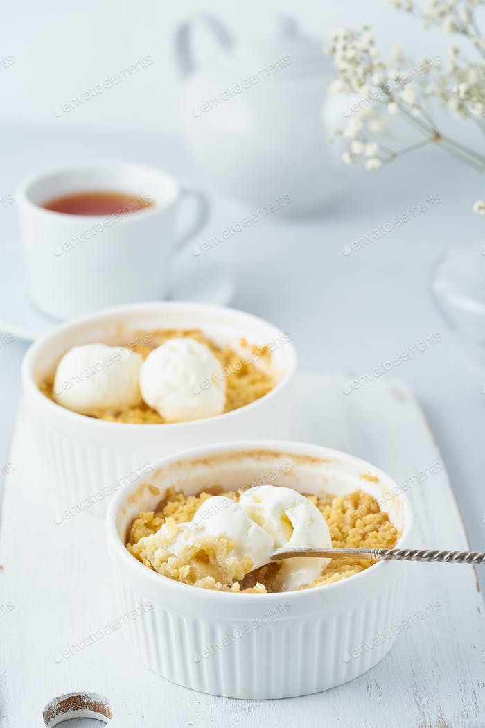 Apple crumble, a spoon with ice cream, streusel. Side view, vertical. Morning breakfast.