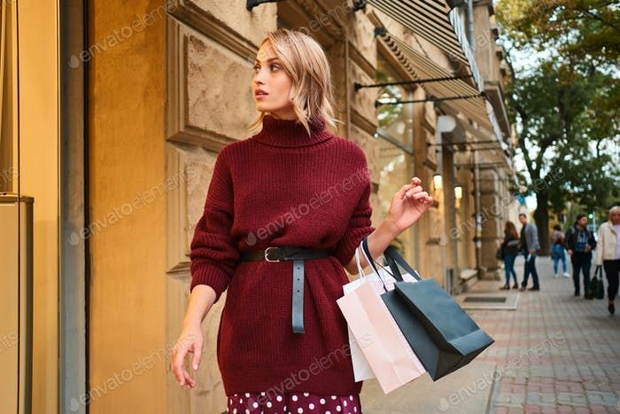 Beautiful stylish blond girl in knitted sweater with shopping bags dreamily walking on city street