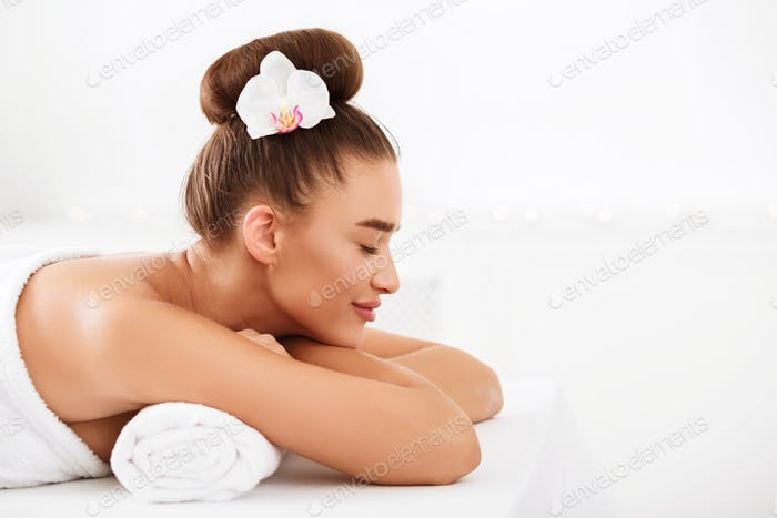 Beautiful girl relaxing at light spa salon, side view