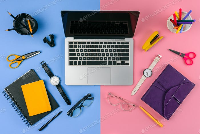 top view of laptop with blank screen, eyeglasses, wristwatches and notebooks divided at male and