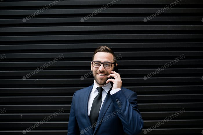 Laughing business man with smartphone