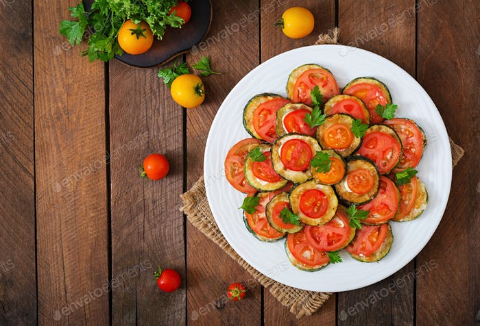 Dish with a snack of fried zucchini with tomatoes. Top view