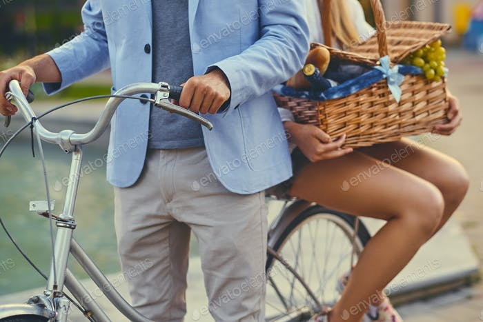 A couple rides a bicycle to a picnic.
