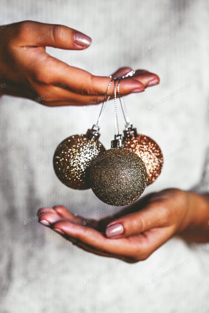Woman in warm sweater holding toys glass decorative balls in hands, copy space. Christmas