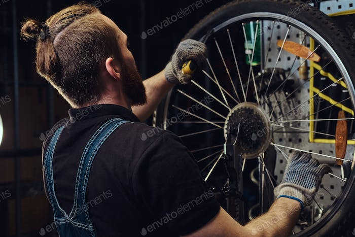 Handsome male with beard and haircut wearing jeans coverall working in a workshop
