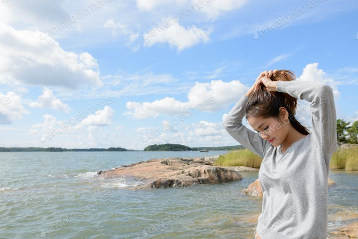 Young beautiful Asian woman against scenic view of the lake