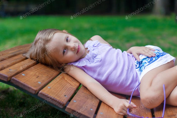 Cute little girl lying on wooden chair outdoor in the park