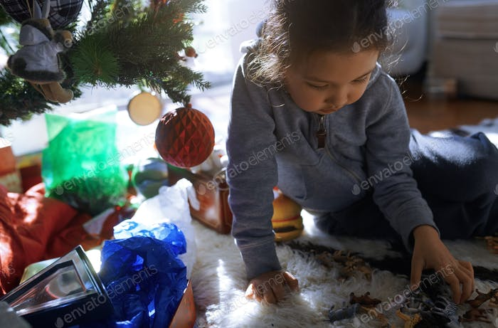 Little girl playing at the Christmas tree