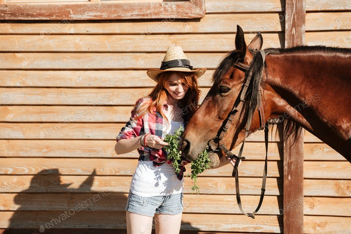 Smiling woman cowgirl giving fresh grass ti her horse