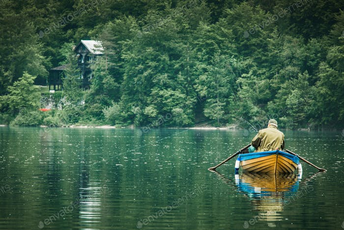 retired old man fishing from boat at lake