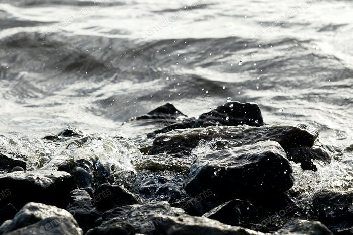 Coastal rocks on wave background