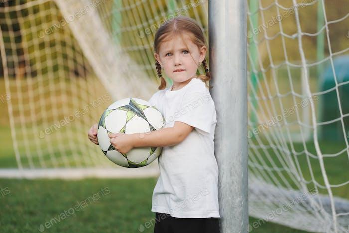 kleines glückliches Mädchen auf Fußballplatz