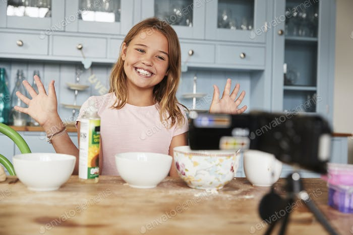 Girl video blogging in the kitchen smiling and showing hands