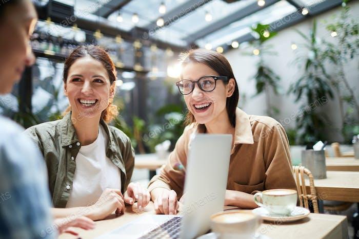 Colegas emocionados Trabajo en Equipo en la cafetería