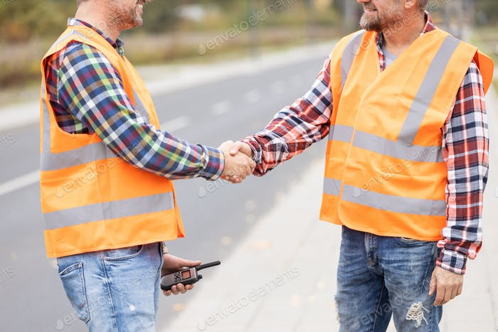 Two builder shaking hand on the road construction field
