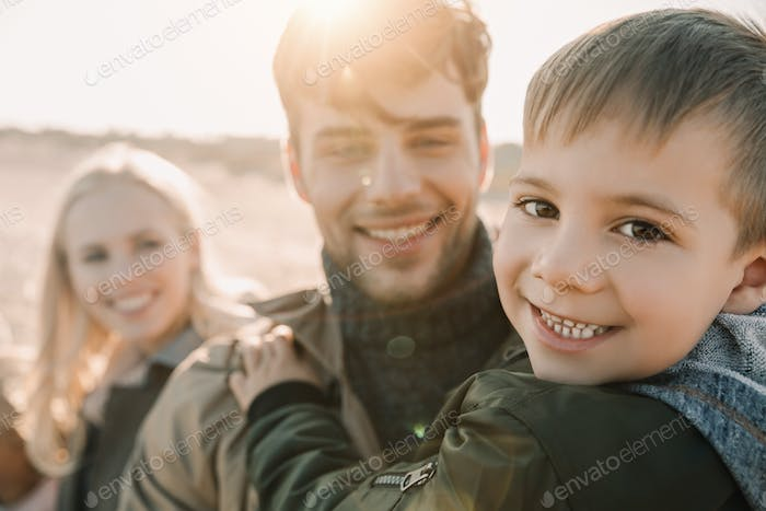 happy family hugging with son on seashore in autumn with backlit