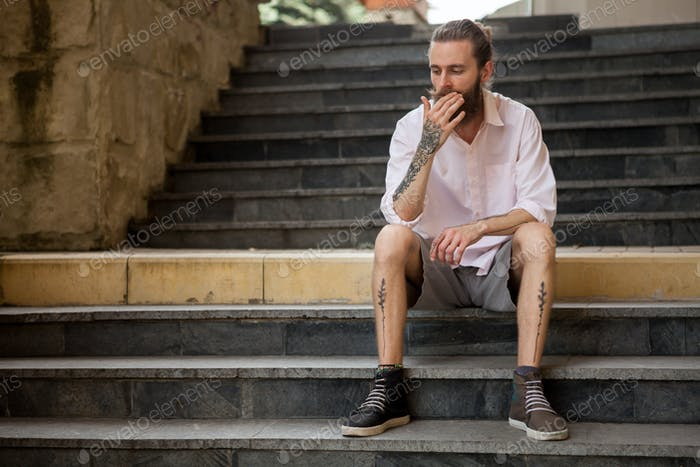 Tattoed and bearded guy posing outdoor