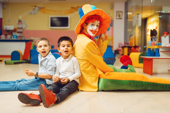 Funny clown play with boys in kindergarten