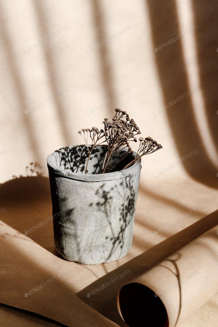 Abstrakte kreative minimale Komposition mit einem Tontopf und trockenem Gras