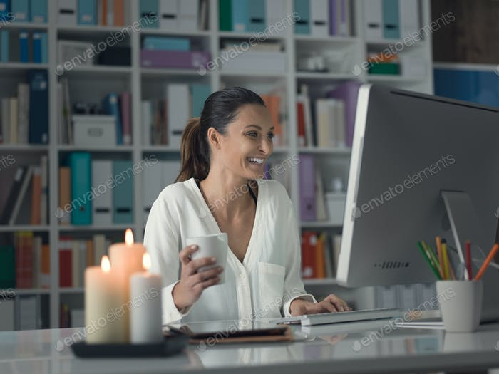 Woman relaxing at home and connecting with a computer