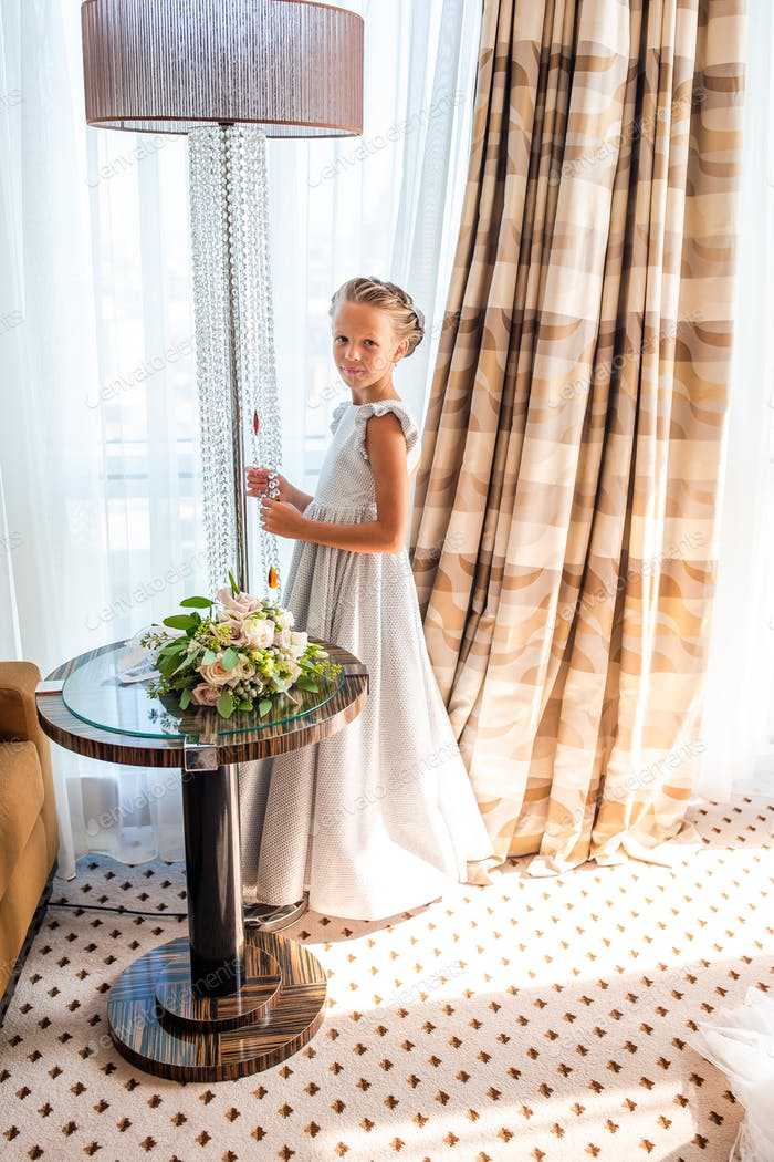 Adorable little girl in amazing dress at a wedding ceremony