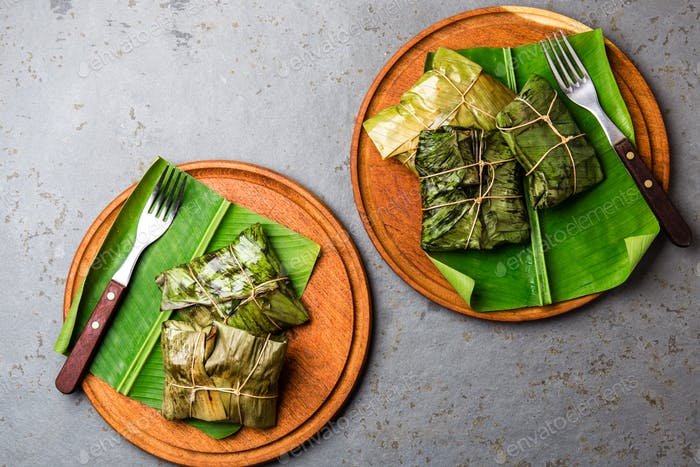 COLOMBIAN, CENTRAL AMERICAN FOOD. Tamales wrapped in banana palm tree leaves on wooden plates, gray