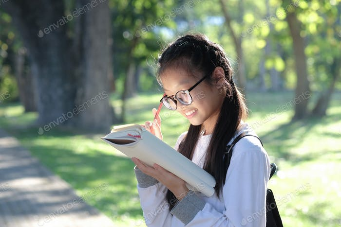 Asian girl student holding pencil and standing reading in garden