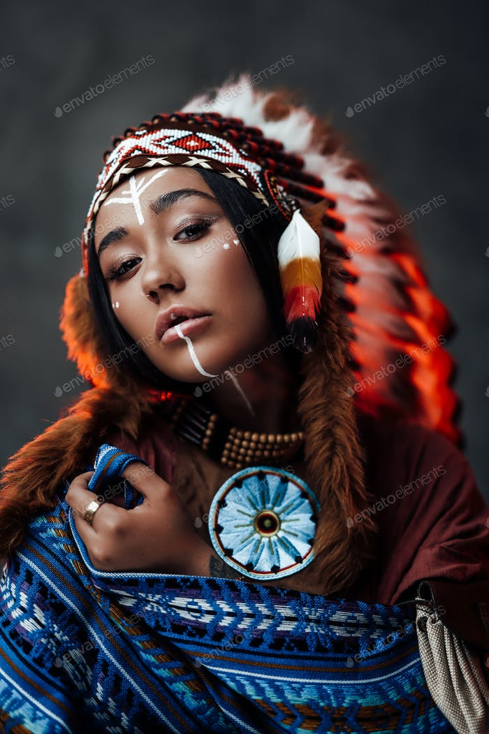 Portrait of a beautiful American Indian woman in ethnical costume and traditional make up