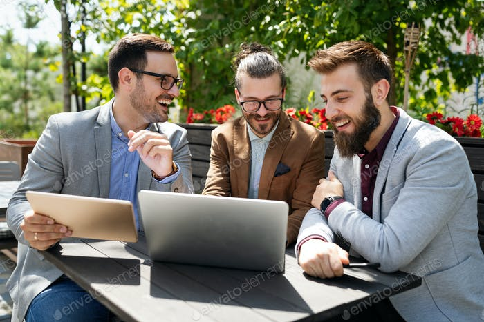 Positive successful business specialists discussing plan with laptop outdoors