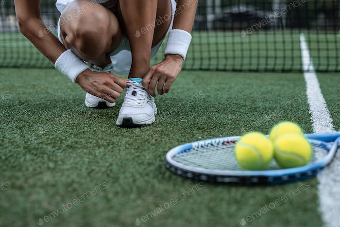 Sportswoman tying the lace on the court