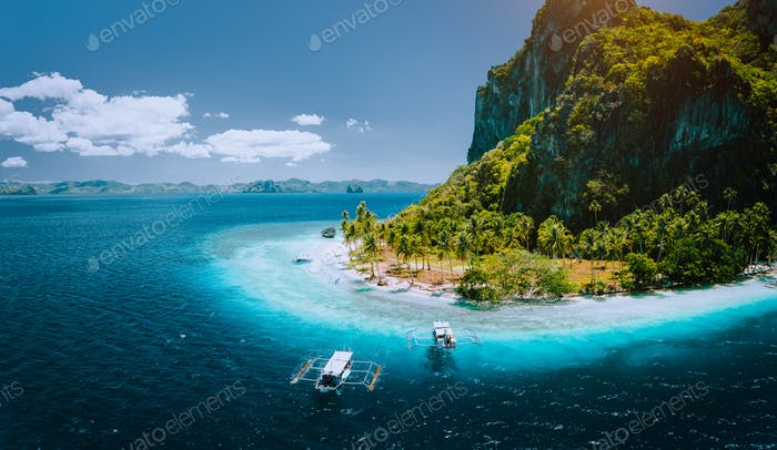 Epic aerial drone panoramic picture of tourist boats arriving tropical Pinagbuyutan Island with