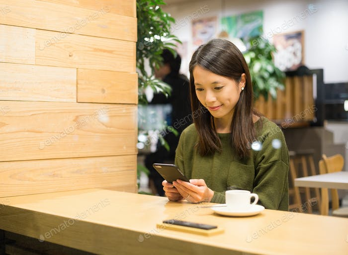 Woman play game on smart phone in cafe