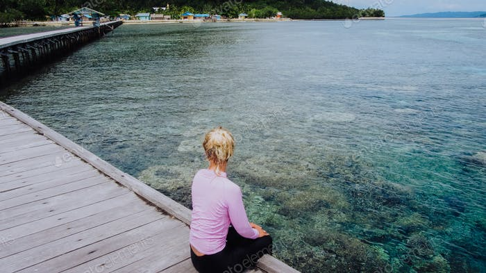 Girl on a wooden jetty near Yenbuba village leading to Mansuar island in Raja Ampat. Beautiful