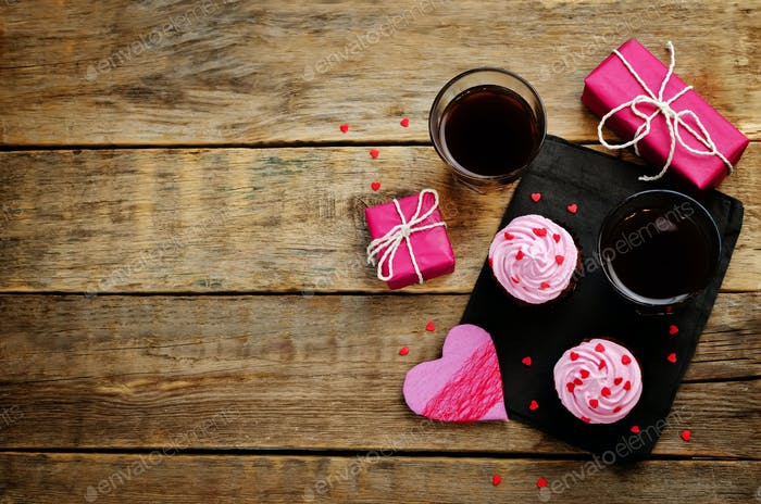 Wood background with gifts, cupcakes, coffee and card